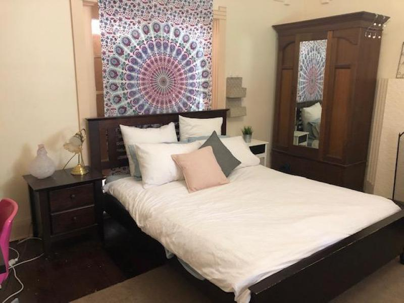Large room with queen size bed, wardrobe, desk and lounge