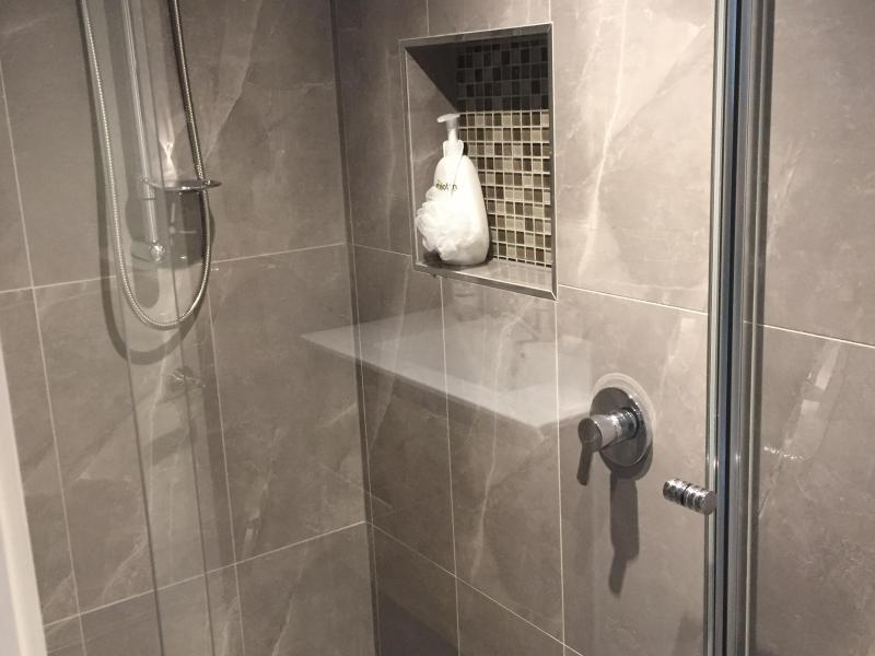 Shower in bathroom. There is also a sink/cupboard unit and large wall mirror in the bathroom
