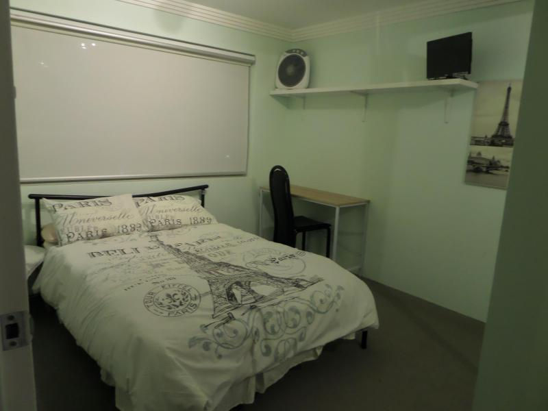 Bedroom with double bed, built-in-robe, tv, desk, lamp.