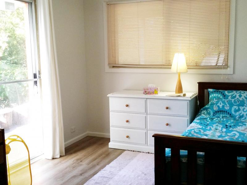 Single bed, bed linen, wardrobe, blinds, timber floor, lock on the door, lamp. dresser with drawers, mirror, a desk, chair, a blanket box.