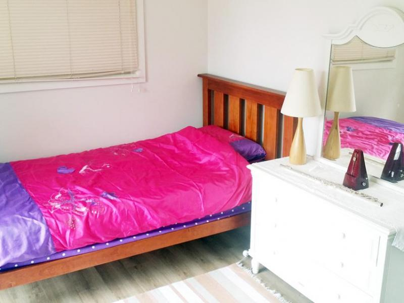 King single bed, bed linen, wardrobe, timber floor, dresser, mirror, lamp. a table, chair.