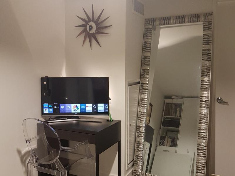 Single bed with TV, computer desk and large mirror in semi-private room