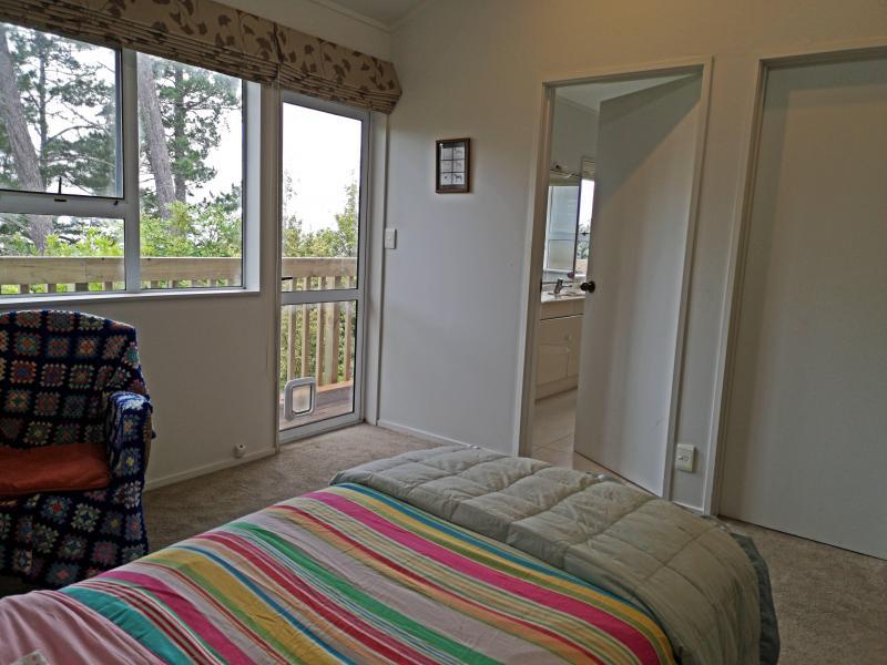 Master bedroom showing outside door, deck, bathroom and door to wardrobe