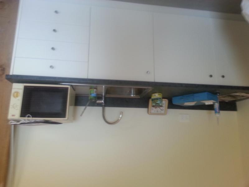 bench with plates etc toaster, microwave, fridge/freezer.