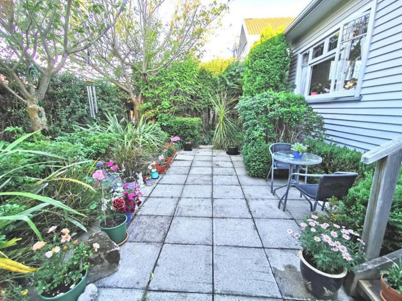 Outside courtyard area with seating area, flowers and veggies growing. I enjoy gardening.