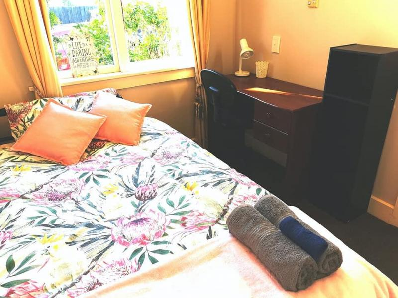 Small and cosy single Bedroom with desk, lamp, chair, shelves, wardrobe, bedding and towels.